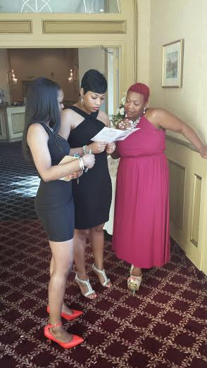 Client Liason Kiara Barnett (left) goes over last minute details with Ketura (center) and the event coordinator Angie at a wedding reception