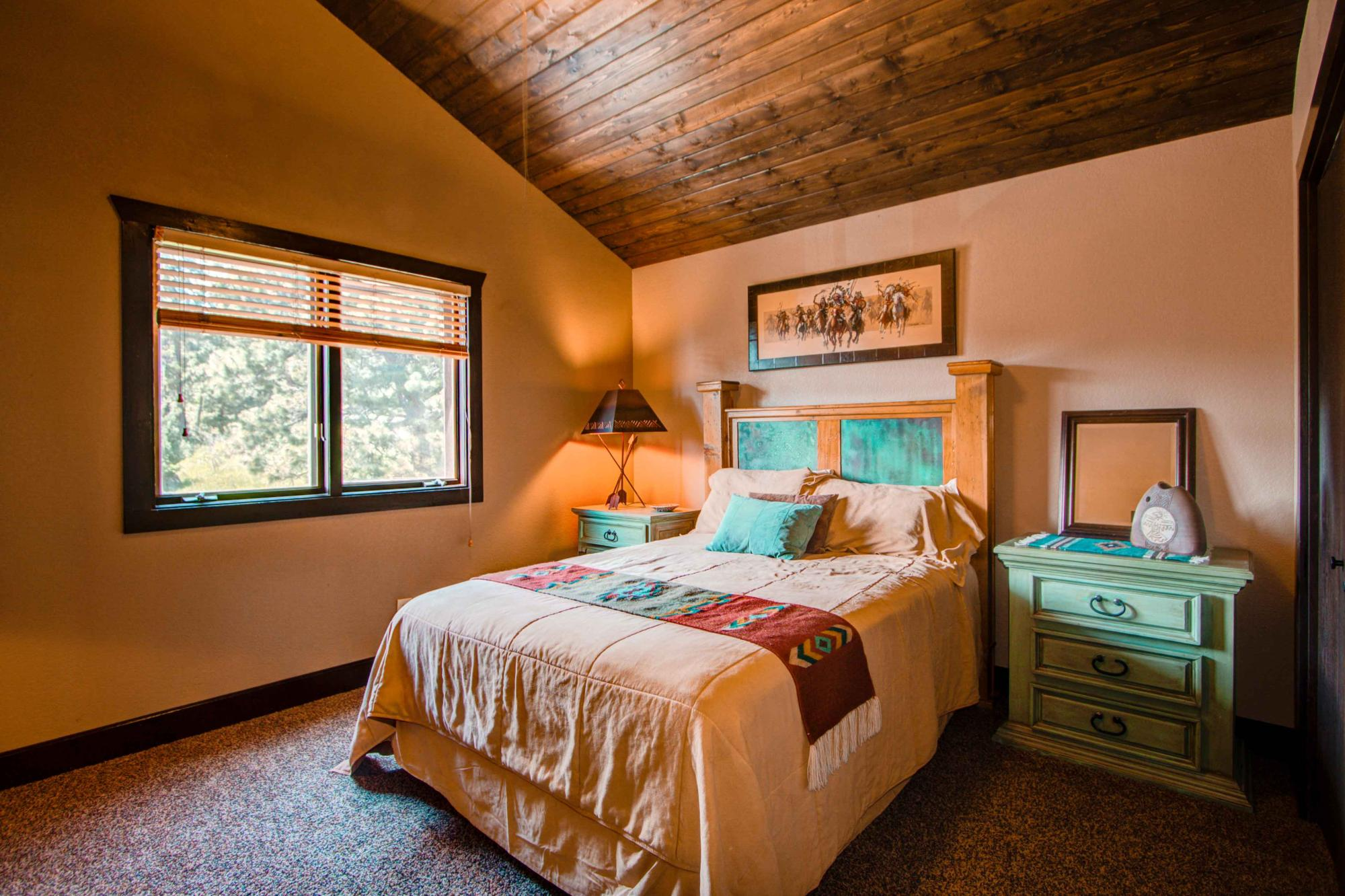 Guest room with queen bed. Notice the high sloped wood ceiling!