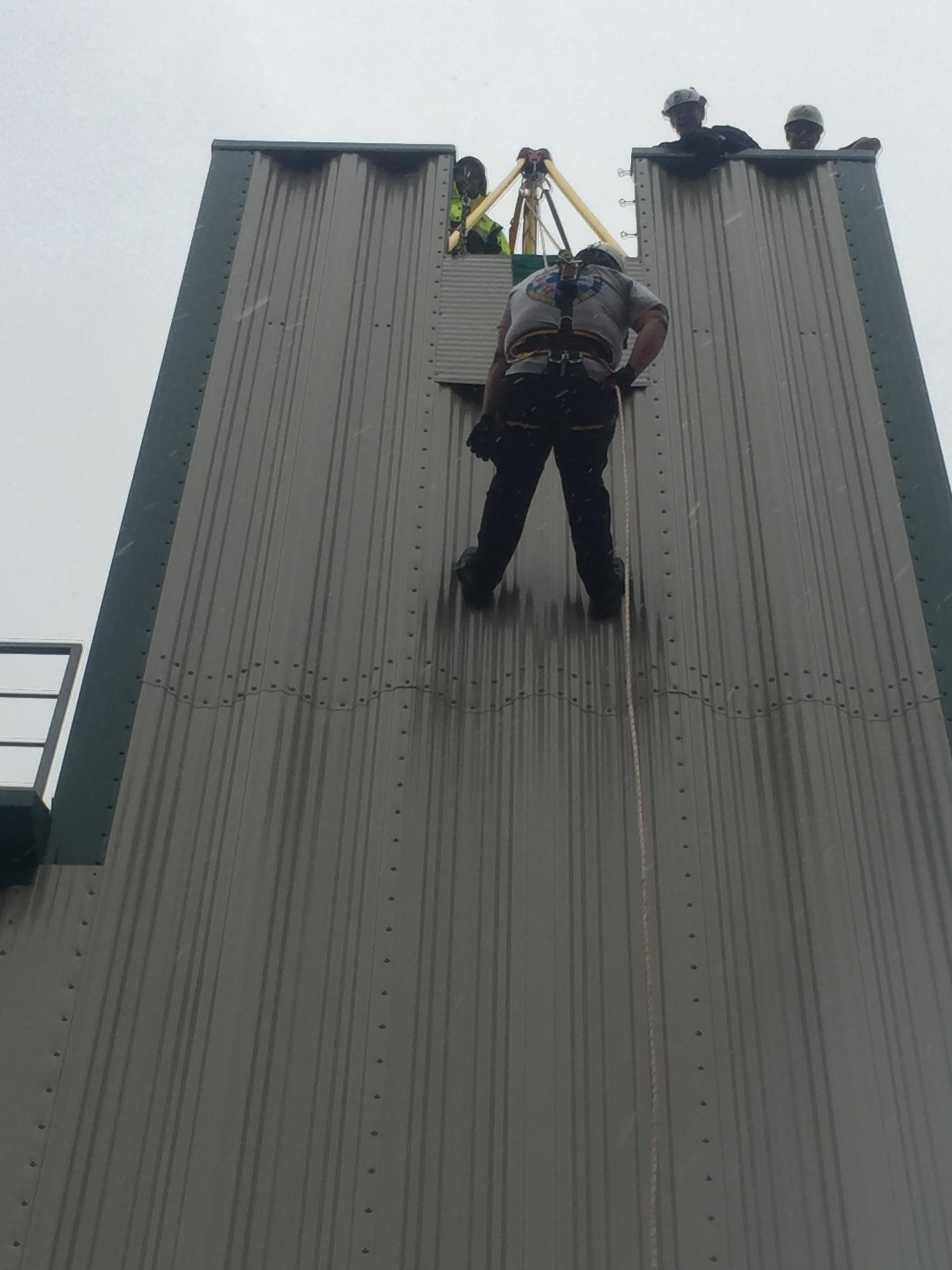 Repelling from the side of the building.